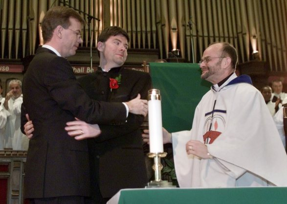 Kevin Bourassa (L) and his partner Joe Varnell are congratulated by Reverend Brent Hawkes (R) during their wedding ceremony  in a Toronto church January 14, 2001. The men were one of two gay couples married in a ceremony at Toronto's Metropolitan Community Church. Both couples were issued marriage licenses believed to be first ever in Canada. The Ontario Provincial government has vowed not to register the marriages.         REUTERS/Andy Clark
